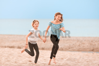 Two young girls running, playing on the beach