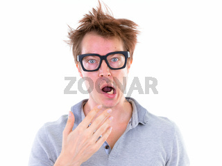 Face of funny young nerd man with big eyeglasses looking shocked