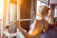 Frau macht Krafttraining am Latzug im Fitnesscenter