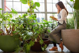 Floristin mit Checkliste kontrolliert Pflanzen