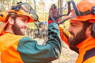 Zwei Waldarbeiter geben sich ein High Five
