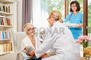 Krankenschwester misst Blutdruck bei einer Seniorin