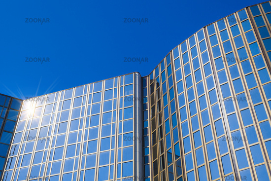 Modern office building with glass facade in front of blue sky
