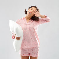 sleepy yawning young woman in pajama with pillow