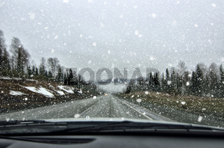 Fahrzeugsicherheit im Winter - unscharfe Ansicht der Straße und der Schneefälle in der Autowindschut