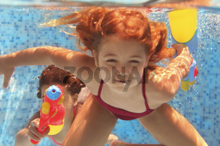 Funny little girls playing with water guns in the pool