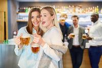 Freundinnen trinken zusammen Bier in einer Kneipe