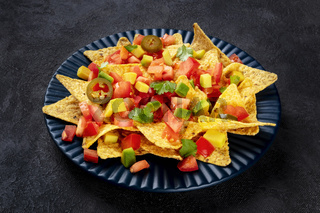 Mexican nachos, tortilla chips with tomato, avocado, and cilantro leaves, a close-up shot on a dark background