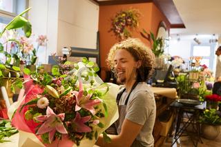 Junger Florist wickelt Blumenstrauß in Papier