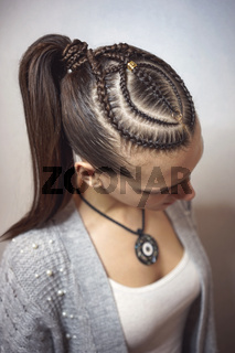 cornrows hairstyle for a girl with dark hair, thin braids tied in a tail