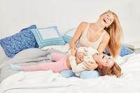 Lachende Mutter beim Auskitzeln ihrer Tochter