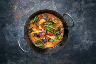 Traditional Thai kaeng phet red curry with vegetables as top view in a wok with copy space