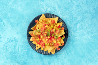 Mexican nachos, tortilla chips with tomato, avocado, and cilantro leaves, shot from the top on a blue background