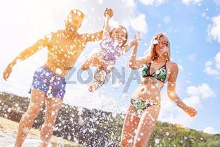 Junge Familie mit Tochter beim Baden im Urlaub