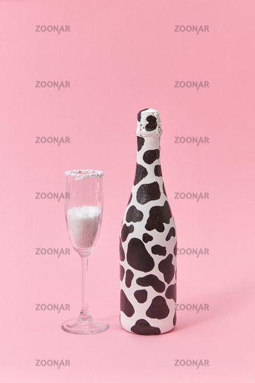 Creative painted wine bottle with black spots and glass of white powder.