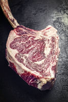 Traditional raw dry aged wagyu tomahawk steak as top view on an old rustic board - vintage
