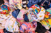 Multiple colors, fabric and textures of woman clothes at a street store.