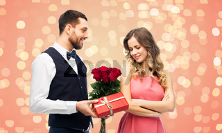 happy man giving woman flowers and present