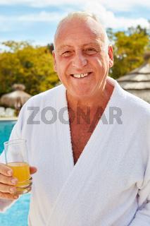 Glücklicher Rentner am Pool mit Orangensaft