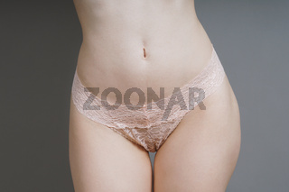 female hips with pink lace panties
