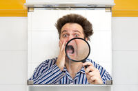 Man in pajamas watching her face in the bathroom mirror