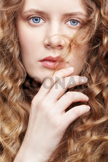 Portrait of a young caucasian woman with long golden wavy hair