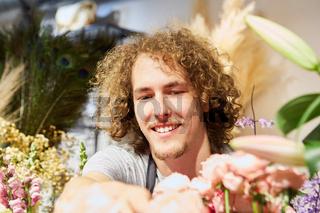 Florist im Blumengeschäft zwischen vielen Blumen