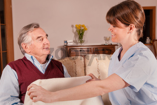 Pflegekraft gibt Senior Decke