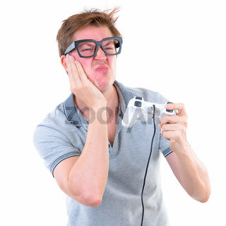 Funny young nerd man with big eyeglasses playing games and losing