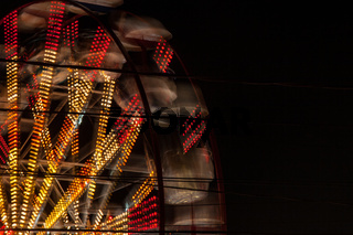 Yellow and red lights of a spinning giant wheel.