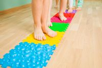 Closeup of kid feet while standing on special massaging mat