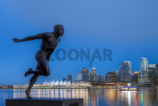 Bronze monument of runner Harry Jerome at dusk, Stanley Park, Vancouver, BC, Canada. Downtown and Canada Place across Coal Harbour in background.