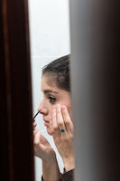 Young girl making up view through the bathroom doorway.