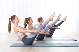 Group of young sporty attractive women in yoga studio, practicing yoga lesson with instructor, forming a line in Navasana, boat asana yoga pose. Healthy active lifestyle, working out indoors in gym