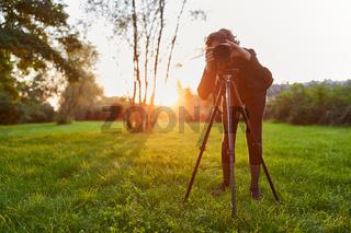 Frau als Landschaftsfotografin mit Kamera auf Stativ