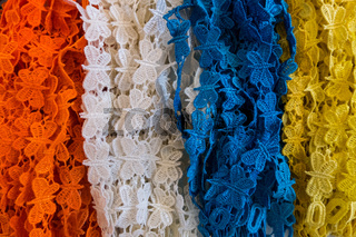 Orange, white, blue and yellow fabric laces.