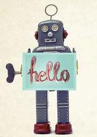 grey retro robot holding a hello sign