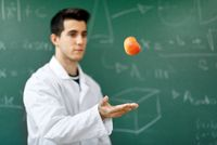 Smiling student with white coat throwing an apple up on green chalkboard with equations background.