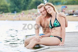 Junges Paar sitzt auf einem Badesteg am See