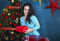 Smiling happy woman with gift box over living room on Christmas tree background