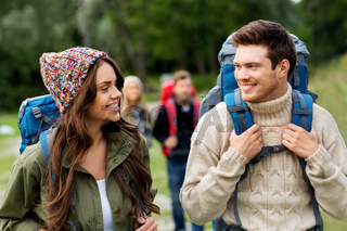happy friends or travelers with backpacks hiking