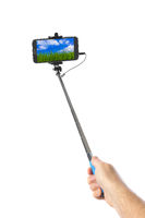 Hand with smartphone selfie stick and landscape (my photo)