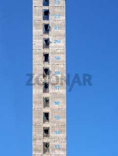 a tall concrete structure and service core of a new skyscraper building under construction with floor numbers marked in paint against a blue sky