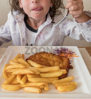 Little Italian girl eating breaded meat and french fries