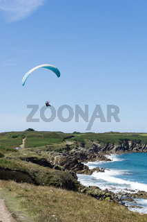 paraglider flying above a picturesque sandy beach on te rocky coast of Brittany
