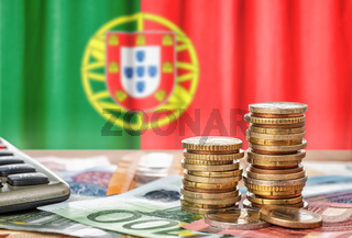 Euro banknotes and coins in front of the national flag of Portugal