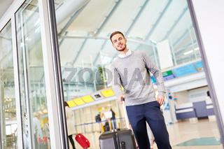 Junger Mann mit Gepäck im Flughafen Terminal