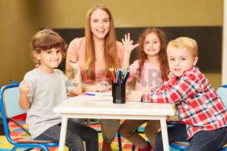 Kinder haben Spaß im Malkurs mit ihrer Erzieherin