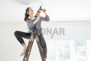 Junge Frau als Heimwerkerin mit Bohrmaschine