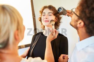 Visagist und Make-Up Artist schminken ein Model